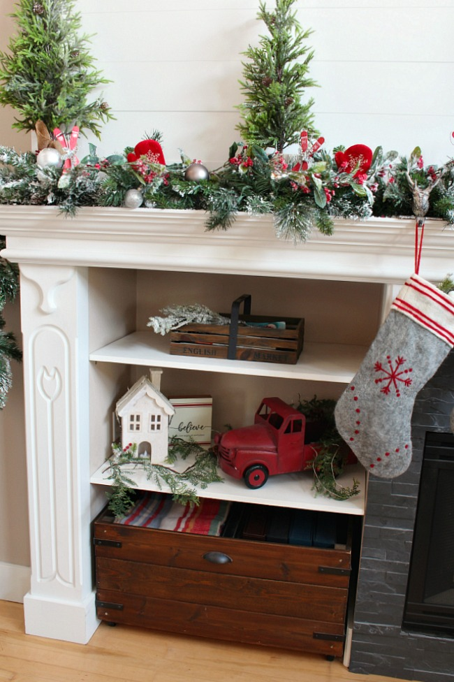 Christmas mantel with shelves decorated for Christmas with vintage truck.