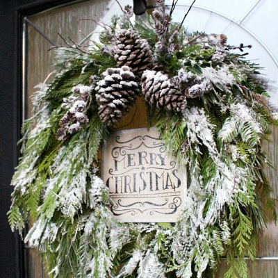 Christmas wreath made from fresh greenery and topped with flocking.