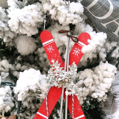 Cute popsicle stick skis Christmas ornament hanging on a Christmas tree.