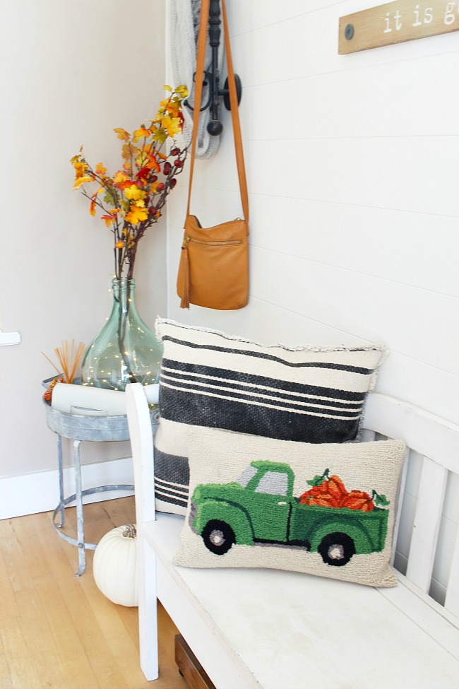 Fall front entry with white bench and farmhouse style fall pillow.