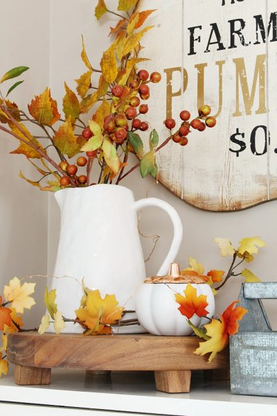 White pitcher with fall leaves.