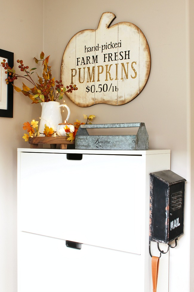 Fall front entry with white Ikea shoe cabinet. Wood tray with some fall stems and a fall candle added for a pretty fall touch.