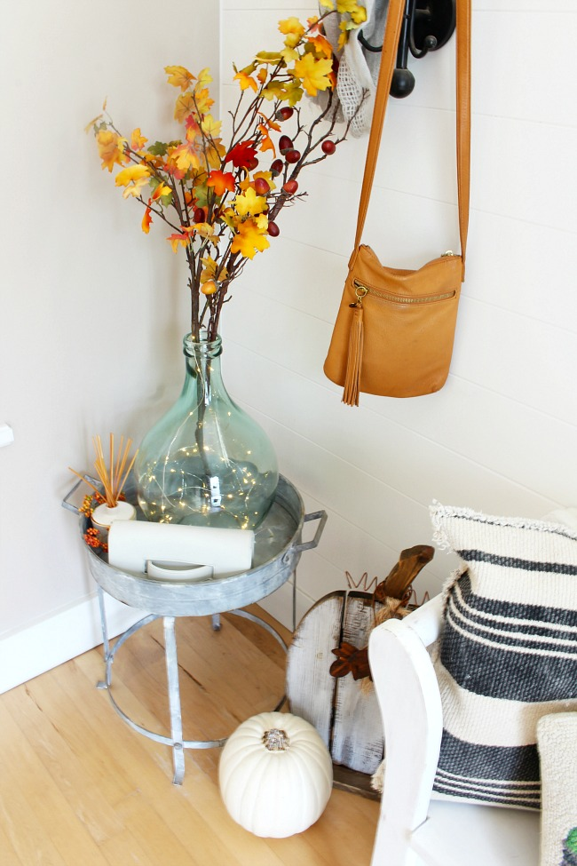 Fall home tour with pretty fall front entry decor. Demijohn bottle on a galvanized tables with colorful fall stems.