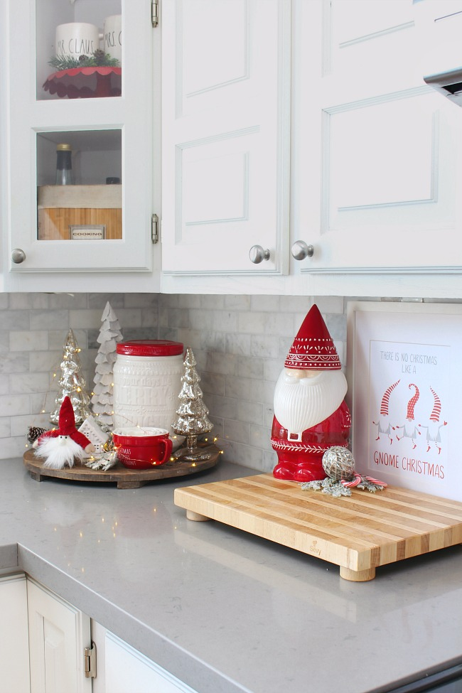 White kitchen decorated for Christmas in red, white, and silver. Cute Christmas gnome accents!