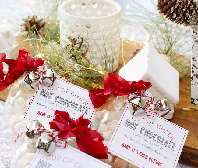 Hot chocolate gift ornaments tied with ribbon, jingle bells and a free printable hot chocolate label. Cute Christmas gift idea!