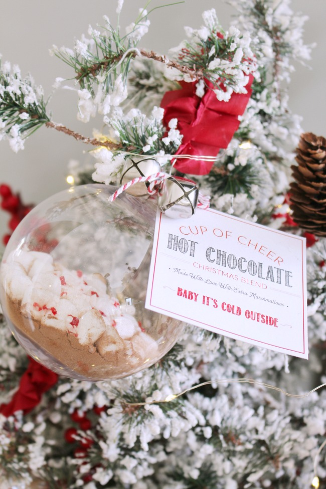 Hot chocolate gift ornament hanging on a Christmas tree. Tied with ribbon, jungle bells and a free printable hot chocolate tag. Cute Christmas gift idea!