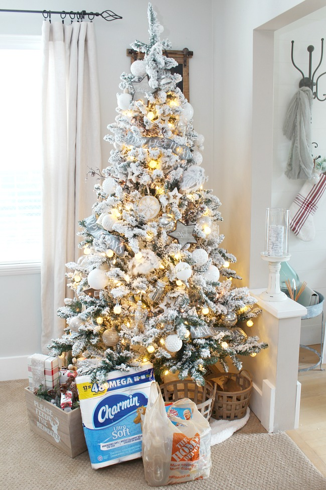 Flocked Christmas tree with a stock of cleaning supplies underneath for the holidays.