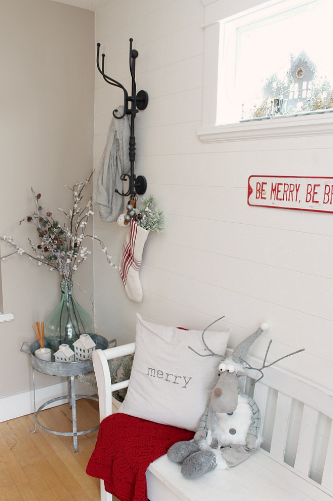 Farmhouse style front entryway with shiplap wall all decorated for Christmas with neutrals and pops of red.