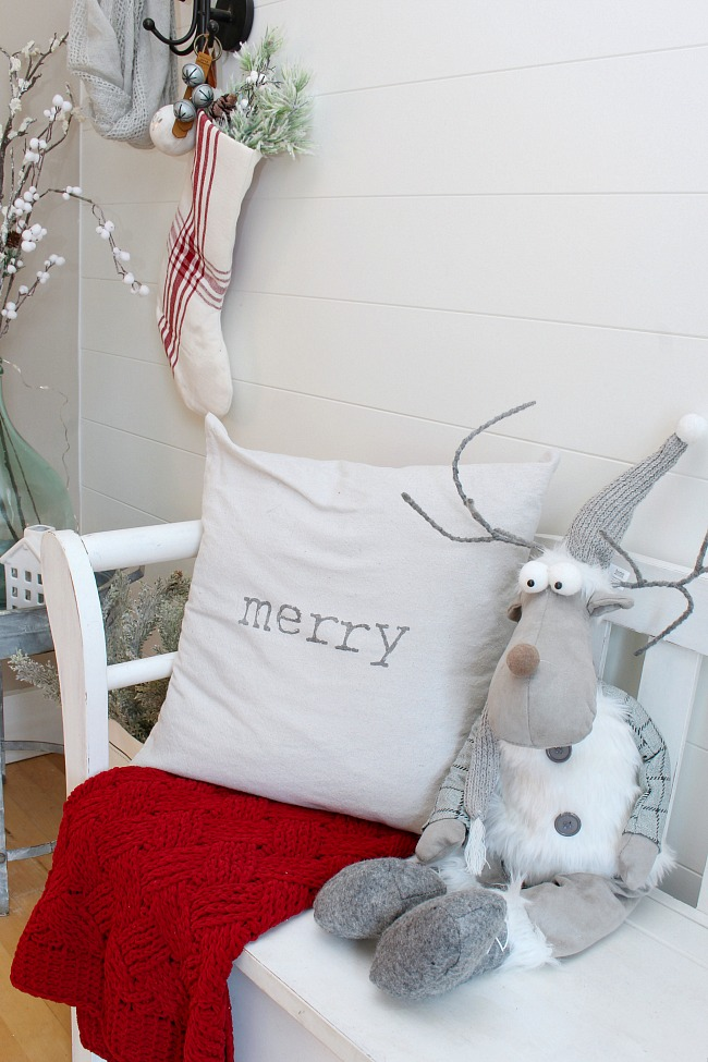 Christmas front entry with white bench, Merry pillow, red, cozy blanket, and a reindeer.