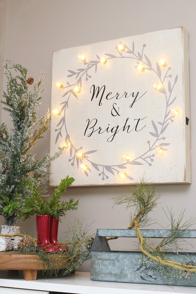 Merry and Bright wood sign with lights in a Christmas front entry.