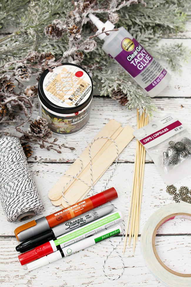 Supplies needed to make popsicle stick skis Christmas ornaments.