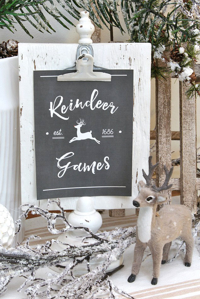 Reindeer games free Christmas printable displayed on a white photo stand.