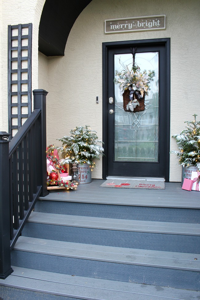Front porch Christmas decorations. Pretty vintage Christmas front porch with basket wreath and flocked trees.