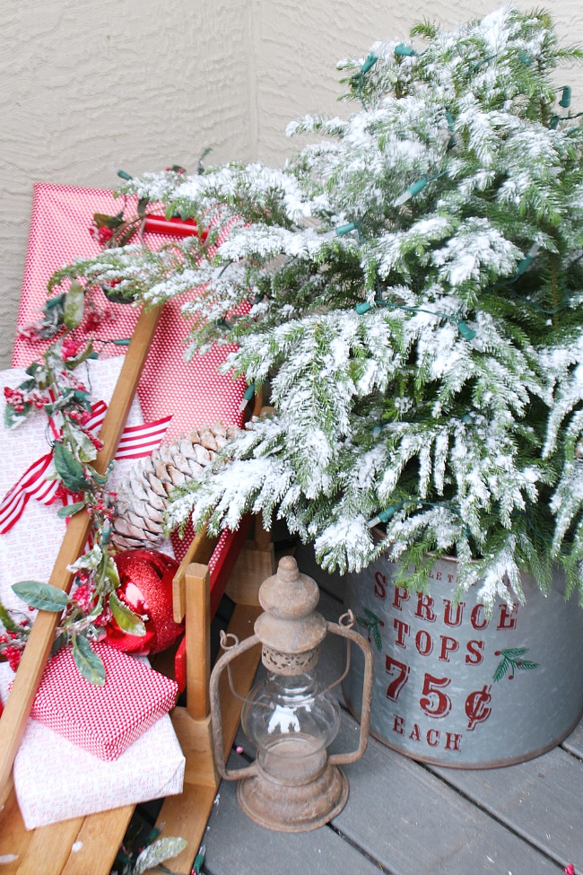 Christmas front porch with flocked tree in a galvanized metal bucket and a vintage sled with pretty wrapped presents.