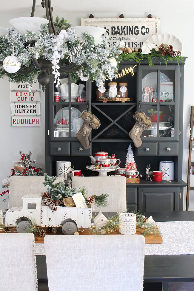 Farmhouse style dining room with black hutch decorated for Christmas in red and white.