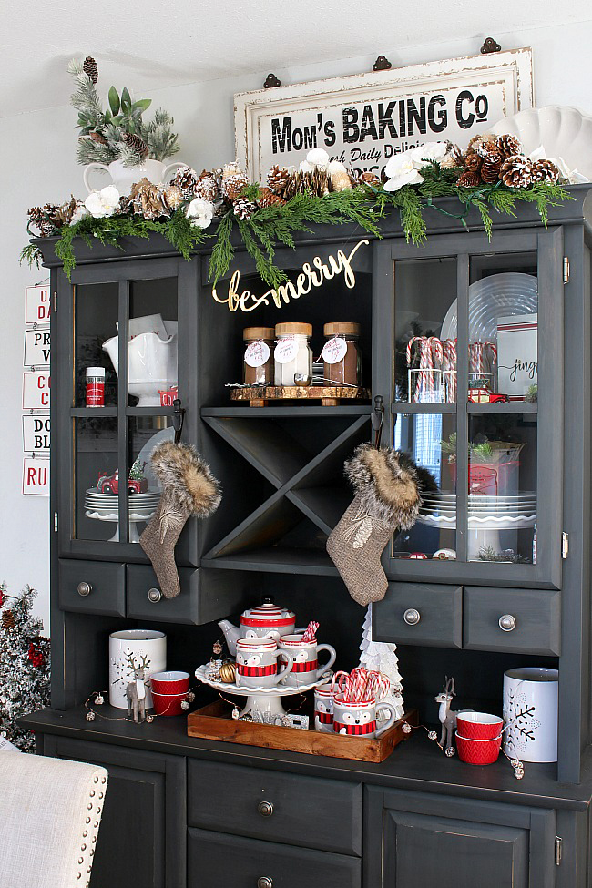 Cute hot chocolate bar set up on a buffet and hutch in a Christmas dining room.
