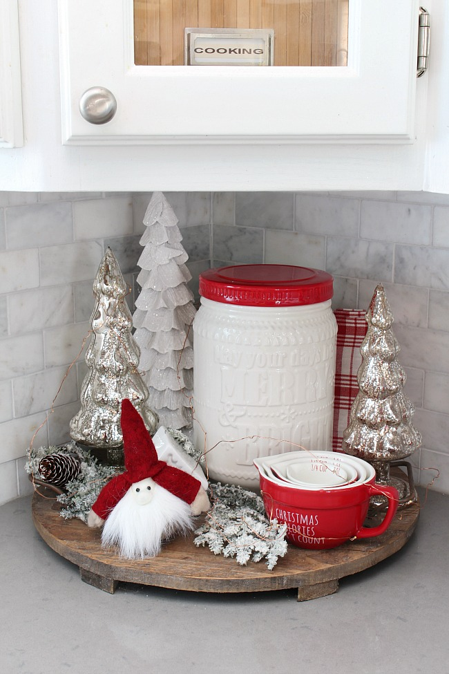 Simple Christmas vignette in a Christmas kitchen using a wood tray, cookie jar and Christmas trees.