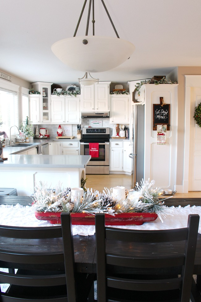 White kitchen decorated for Christmas with traditional Christmas colors.