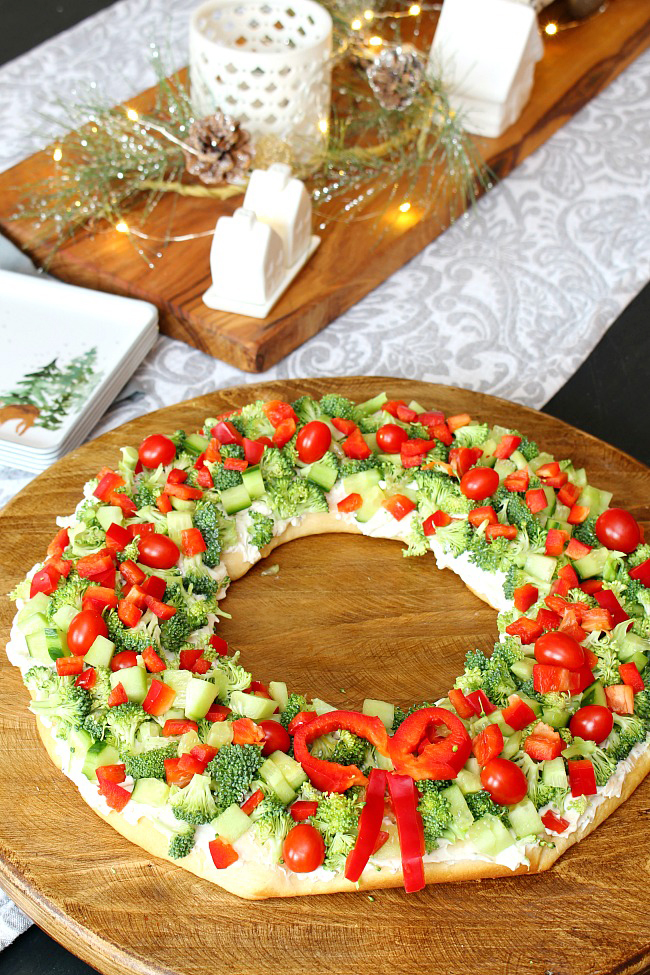 Christmas wreath veggie pizza on a cutting board.