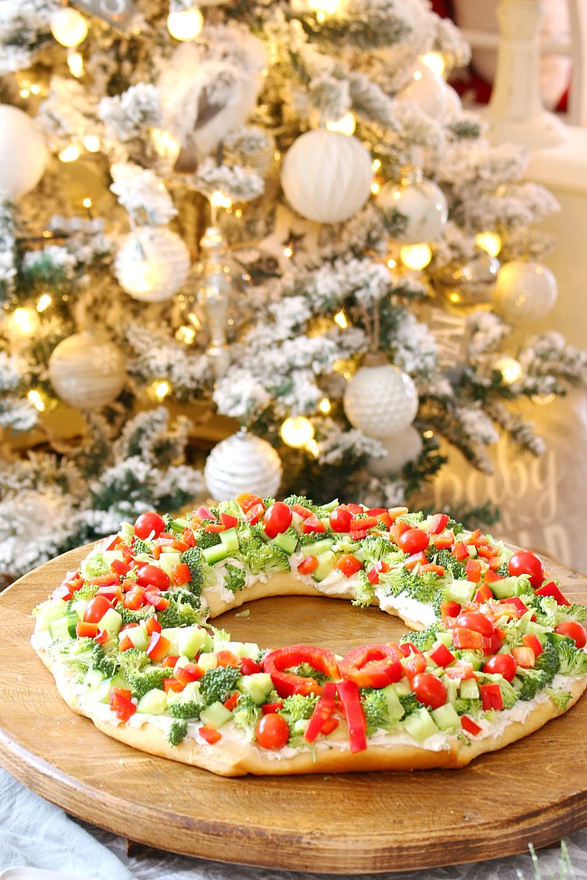 Christmas wreath veggie pizza on a wood cutting board in front of a Christmas tree.