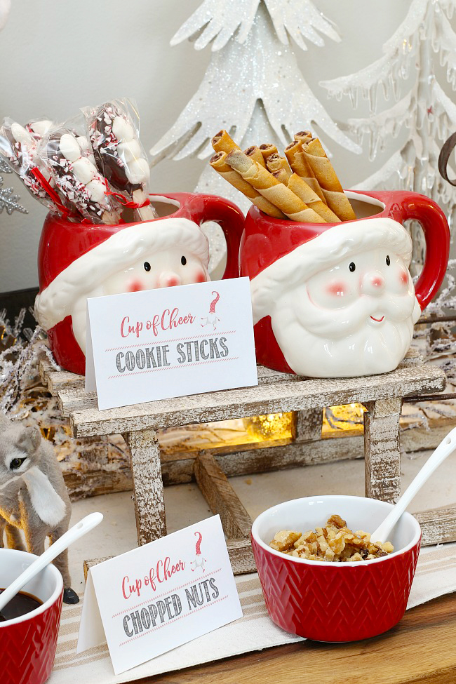 Helpful hot chocolate bar ideas Santa mugs used to hold supplies for a hot chocolate bar with free printable hot chocolate bar labels.