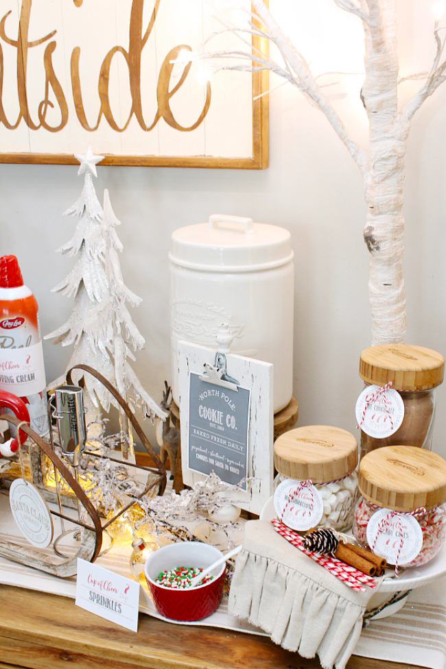 Cute hot chocolate bar on a side board all decorated for Christmas. Free printable North Pole Cookie Co. sign and hot chocolate bar labels.