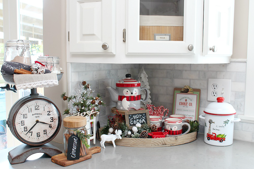 Cute Christmas hot chocolate bar with racoon teapot and mugs in the corner of a kitchen.
