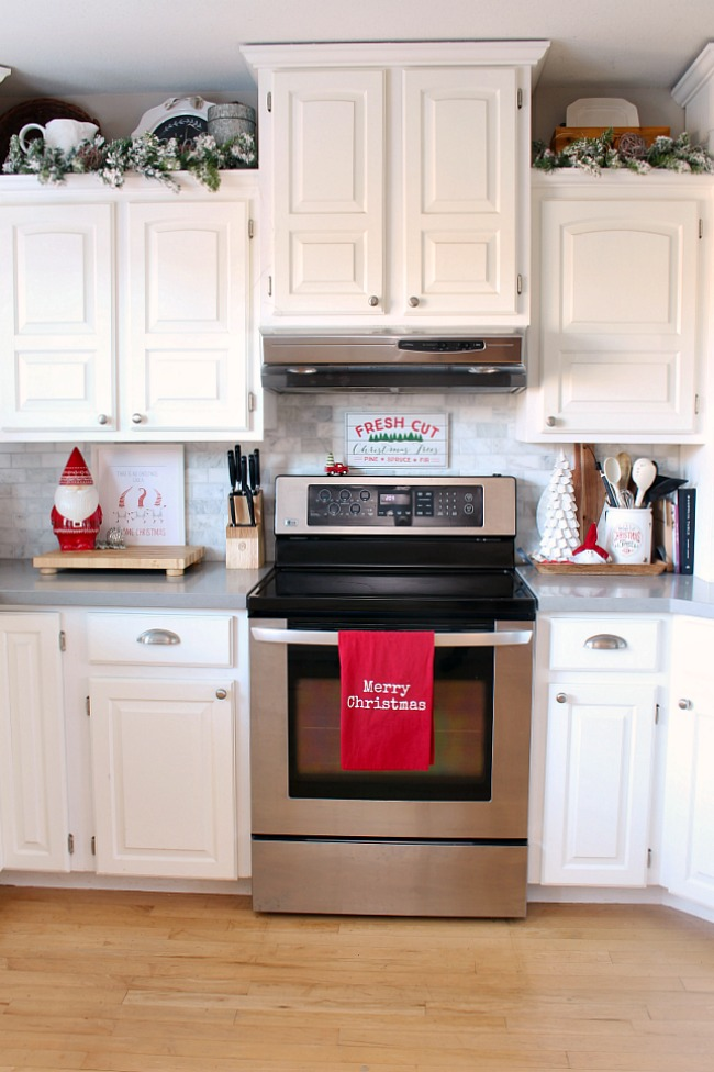 White kitchen decorated for Christmas with traditional Christmas red and Christmas gnomes.