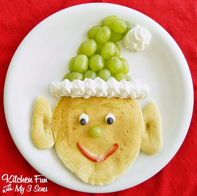 Santa's Elf pancakes with pancakes, grapes, and whipping cream.
