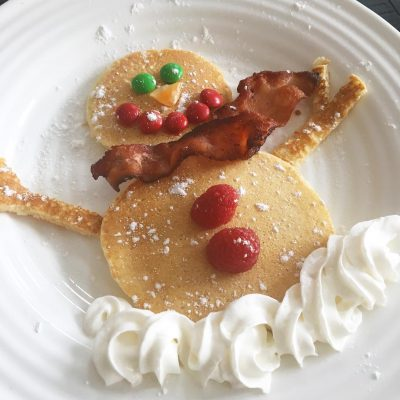 Snowman pancakes with pancakes, bacon, and whipping cream.