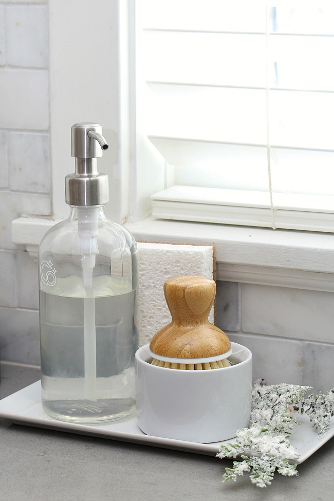 Sink side tray beside the kitchen sink to keep dish soap, scrub brush, and sponge organized.