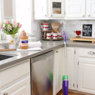 White kitchen with hardwood floors and Swiffer wet jet cleaner.