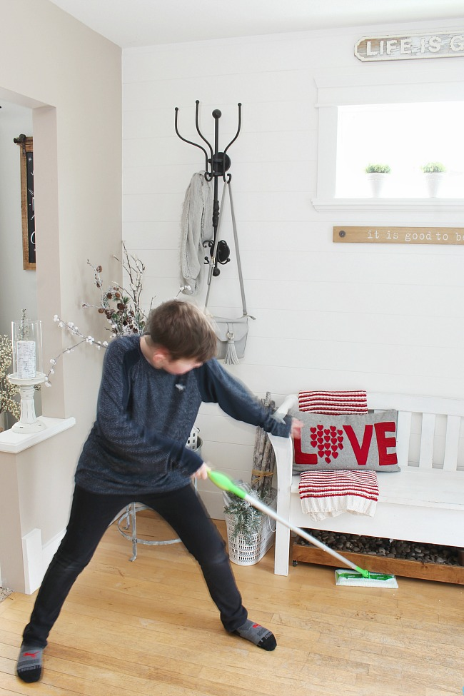 How to clean wood floors. Boy using a Swiffer Sweeper in a front entryway.