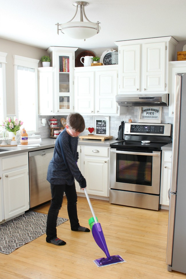 How to clean wood floors. Boy using Swiffer Wet Jet in a white kitchen.