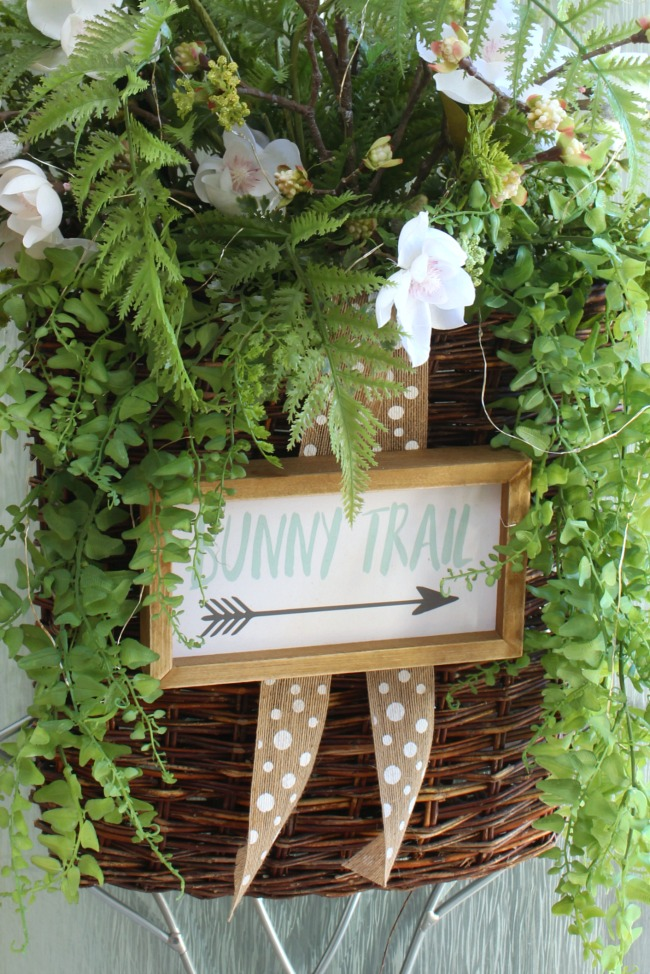 Spring basket wreath with wood bunny trail sign.