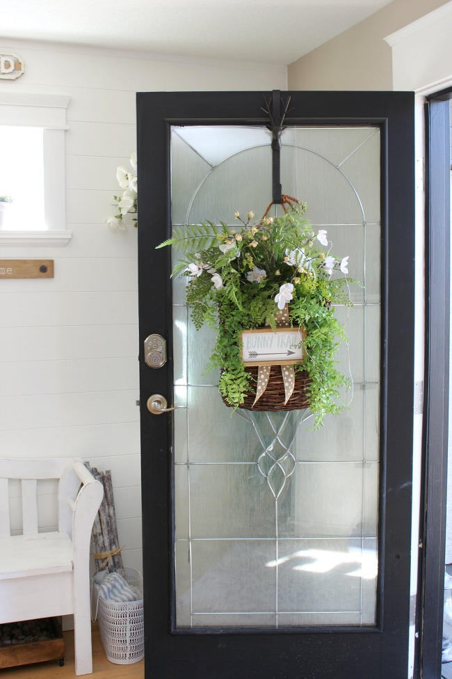 Pretty DIY spring basket wreath hanging on a front door.