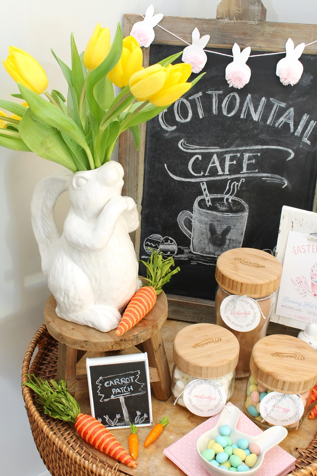 Easter hot chocolate bar with white ceramic bunny pitcher, rustic chalkboard, mason jars, and free printable hot chocolate labels.