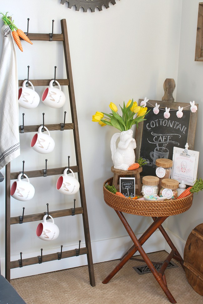 Easter hot chocolate bar and Easter mugs hanging on a decorative ladder.