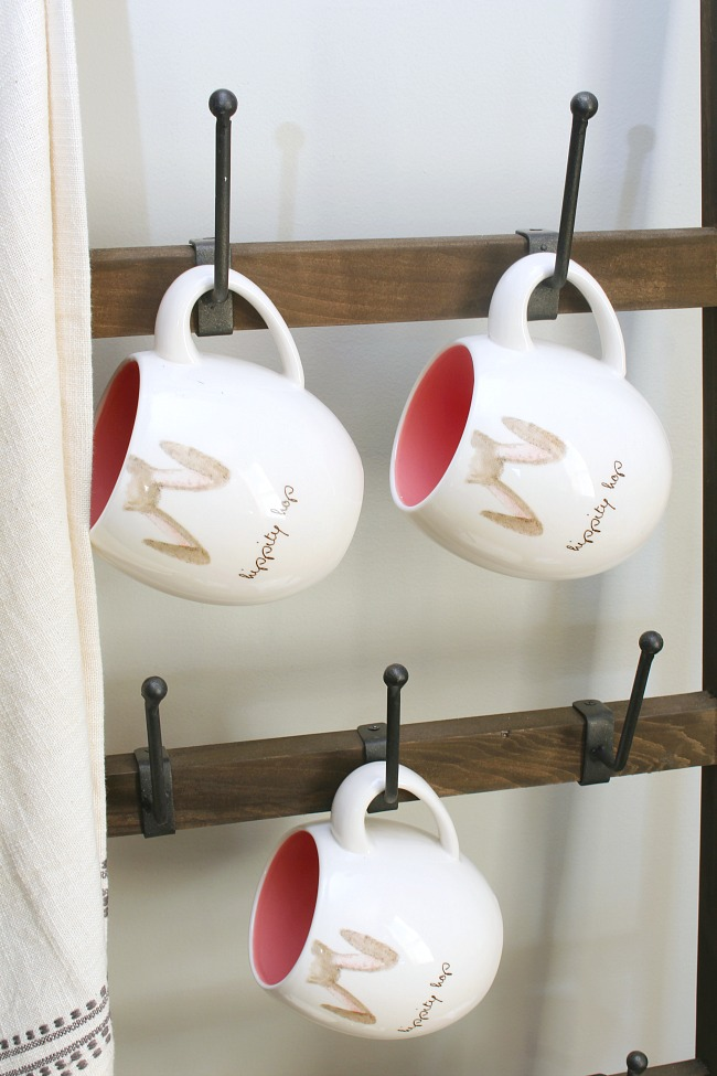 Cute Rae Dunn Easter mugs on a rustic mug ladder.