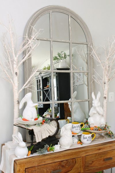 Dining room sideboard decorated for spring with white ceramic bunnies and twinkle light trees.