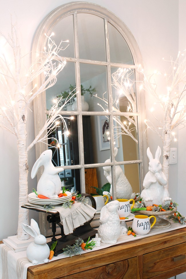 Dining room sideboard decorated for Easter with twinkle light trees and white ceramic bunnies.