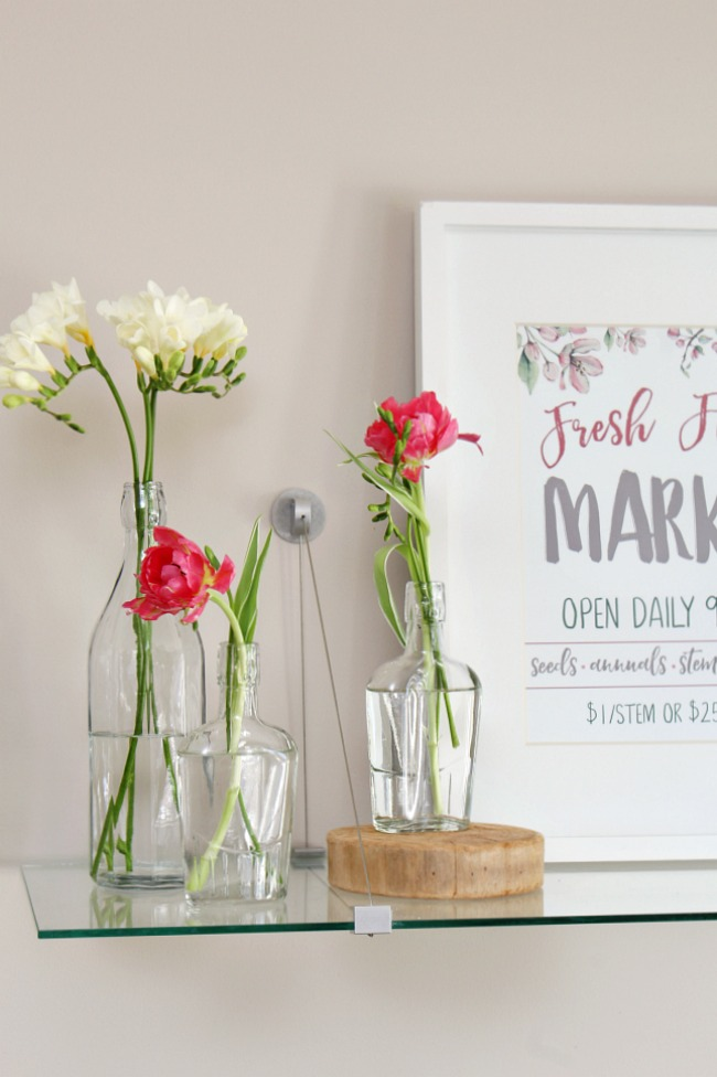 Fresh Flower Market free spring printable and pretty spring vignette with glass bottles and single stem flowers.