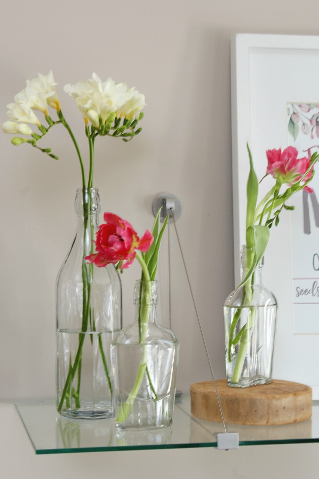 Pink tulips and white freesia in glass bottles.