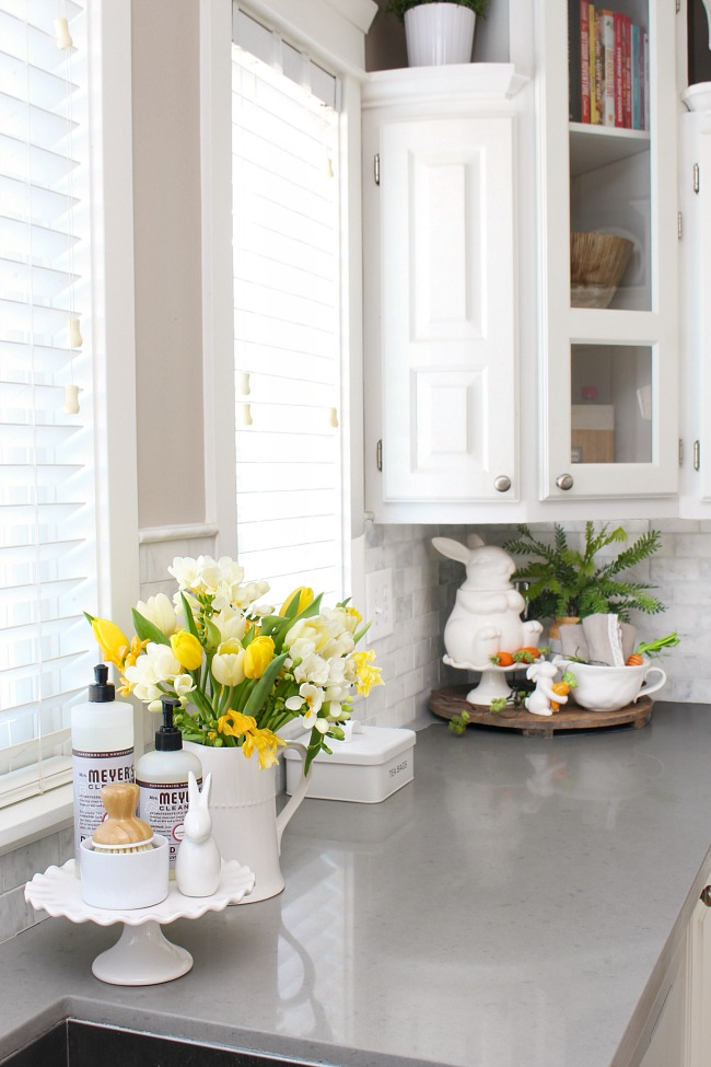 White kitchen decorated for spring with fresh tulips and freesia.
