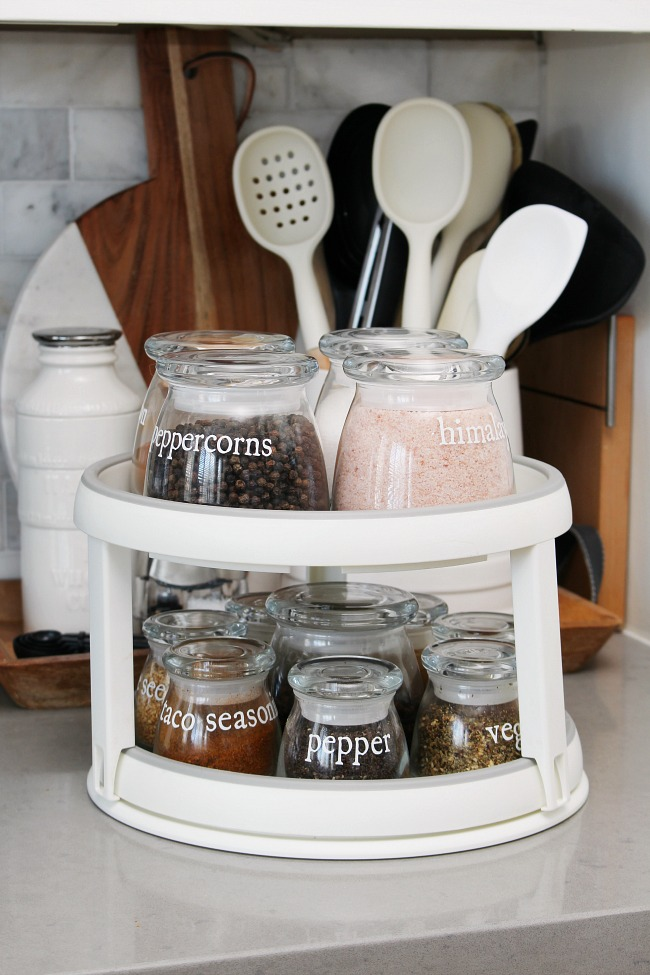 Double lazy Susan holding spices in glass jars with DIY vinyl labels.