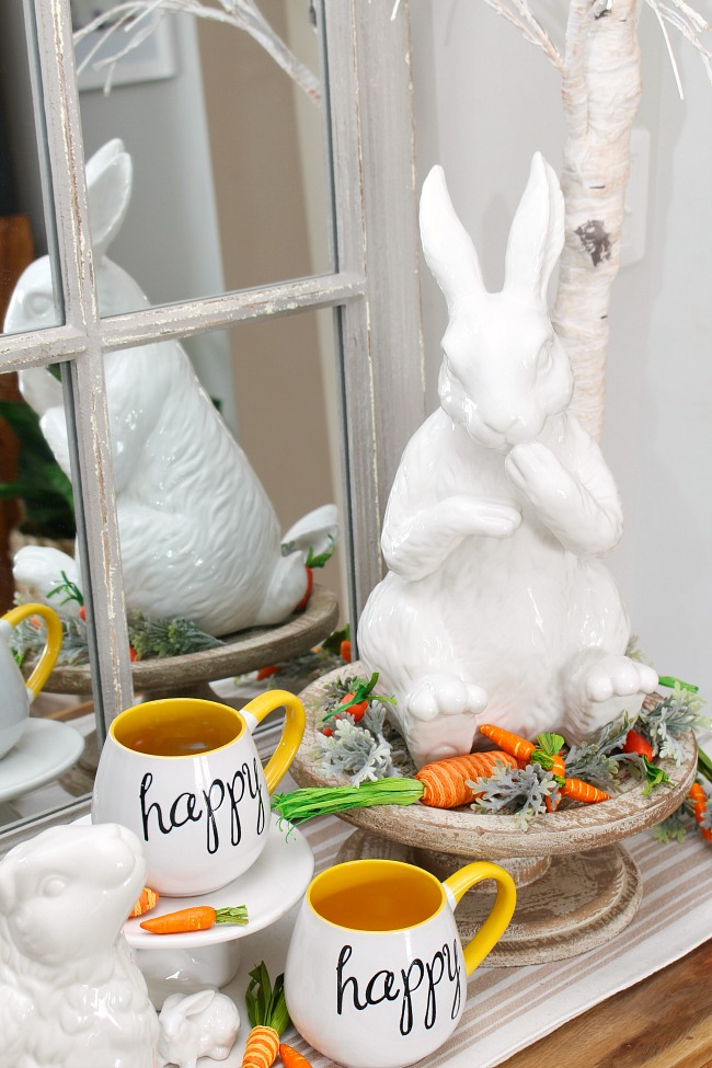 Spring vignette with a white ceramic bunny on a wood cake stand.