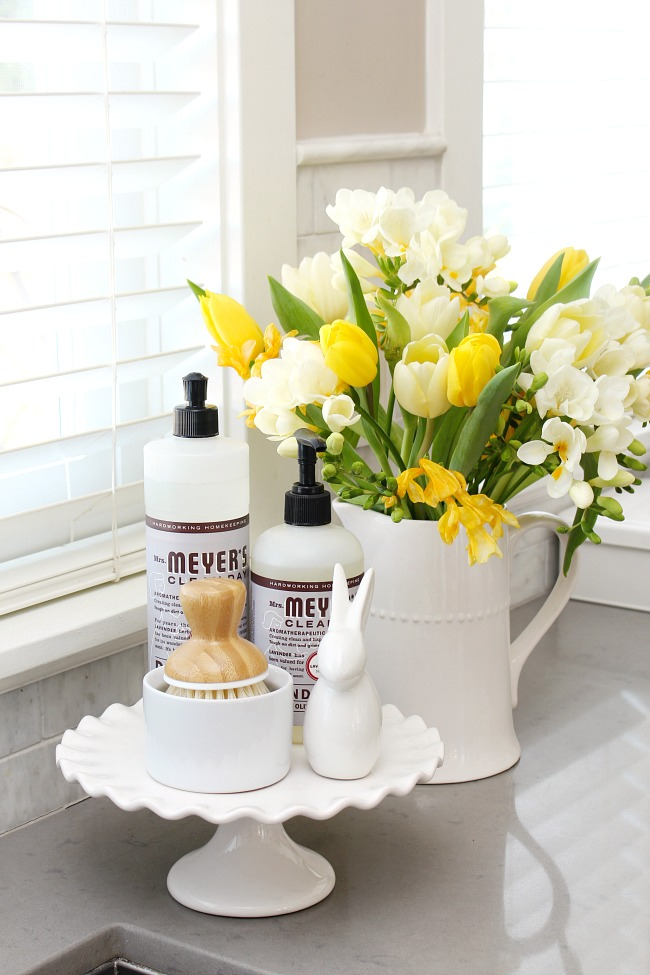 Spring kitchen decor using a white cake stand and white ceramic bunny with kitchen cleaning products.