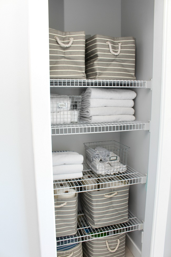 Organized linen closet with wire shelves and striped grey bins.