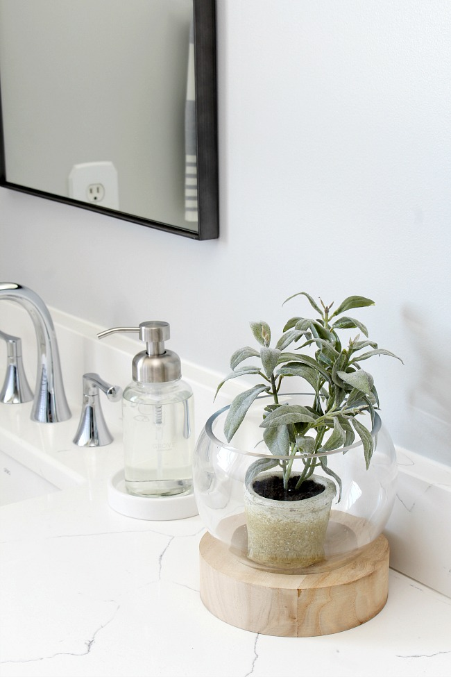 Glass and wood plant holder in a coastal style bathroom.