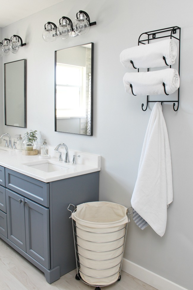 Coastal style bathroom with soft greys and black and chrome accents.